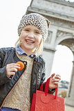 smiling child near Arc de Triomphe holding French macaroon