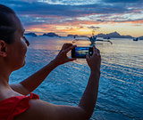 Woman taking pictures at sunset