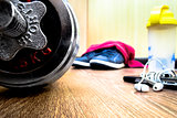 sports equipment on the wooden floor with sneakers, telephone, h