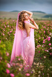 beautiful sexy girl in a pink dress standing in the garden roses