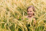 Young girl among the ripening grains of a wheat field
