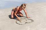 Love the sea - little girl drawing heart shape in the sand