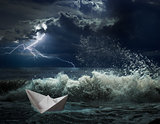 paper boat in ocean storm with lgihting and waves