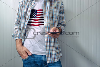 Casual man with USA flag on shirt using mobile phone