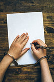 Female hands cuffed signing confession, top view