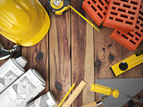 Construction tools on a wooden background. Hard helmet, bricks,