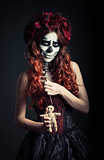 Young voodoo witch with muertos makeup (sugar skull) holds voodoo doll and needle