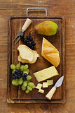 cheese board with grapes, pear and baguette