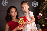 Happy woman and small girl with Christmas gift