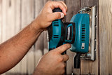 Male hands using a vibrating sander on wooden surface