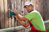 Worker polishing old wooden fence with power tool - a vibrating