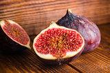 Ripe seasonal figs on a wooden surface.