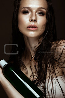 Beautiful girl with a bright make-up, wet hair and skin, bottle of cosmetic products in hands. Beauty face.