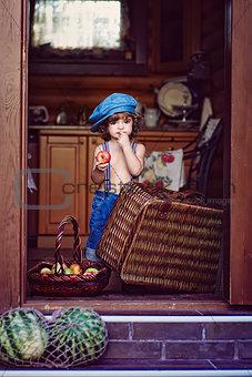 Little boy in a jeans cap holding apple