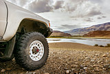 Big SUV car wheel on backdrop of lake