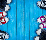 Youth colored sneakers on a blue background of the wooden planks