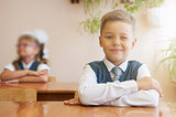 Happy schoolboy sitting at desk