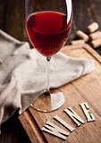 Glass of red wine on wooden board with letters and corks