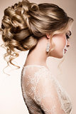 Beautiful bride with fashion wedding hairstyle - on beige background.