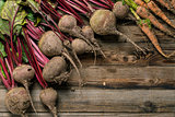 Young beets and carrots on wooden table