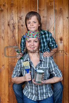 Boy helping his mother painting the tool shed
