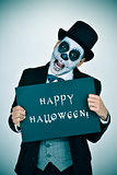 man with calaveras makeup and signboard with text happy hallowee