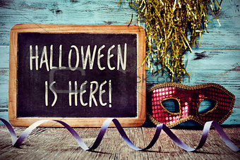 mask and text Halloween is here in a chalkboard