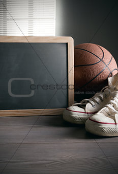 Blackboard with canvas shoes and basketball