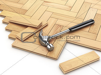 Laying hardwood parquet concept. Hammer on the floor.