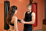 Young woman training in the gym with trainer
