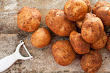 Pile of round baking potatoes beside peeler