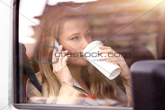 business woman having coffee in the car