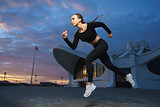 Happy girl run outdoor at modern urban area during sunset.