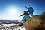 Happy snowboarding couple on the top of winter mountains