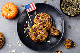 Pumpkin cookies with cranberries and maple glaze with American flag Grey stone background. Top view