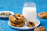 Pumpkin, oat cookies with cranberries, maple glaze and glass of milk on a blue textile background.