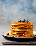 Pumpkin pancakes with maple syrup and blueberries on a plate. Grey stone background Copy space