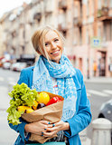 young pretty blond woman with food in bag walking on street