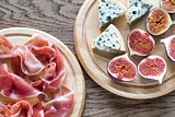 Slices of jamon with blue cheese and figs on the wooden board