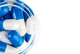 Blue white capsules in clear glass container top view