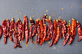 Dried red chili peppers on slate background. Copy space Top view