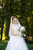 Beautiful bridal bouquet in hands of young bride dressed in white wedding dress.