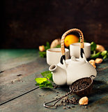 Teapot and cups of tea with mint and lemon