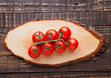 Fresh tomatoes on wooden board and grunge background