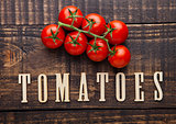 Fresh tomatoes on wooden board with letters below