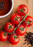 Fresh tomatoes with sause and spoon with pepper kitchen board