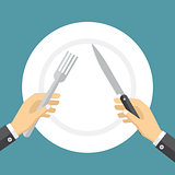 Empty plate and hands holding knife and fork.
