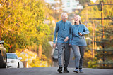 Laughing couple walking along street on hill