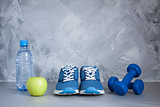 Sport shoes, dumbbells, apple, bottle of water on gray concrete