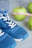 Sport shoes, meter, apples, bottle of water on gray concrete bac